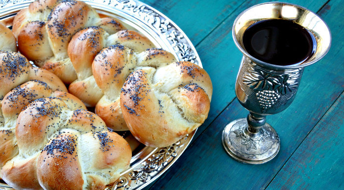 Two loaves of challah on a silver platter next to a cup of wine