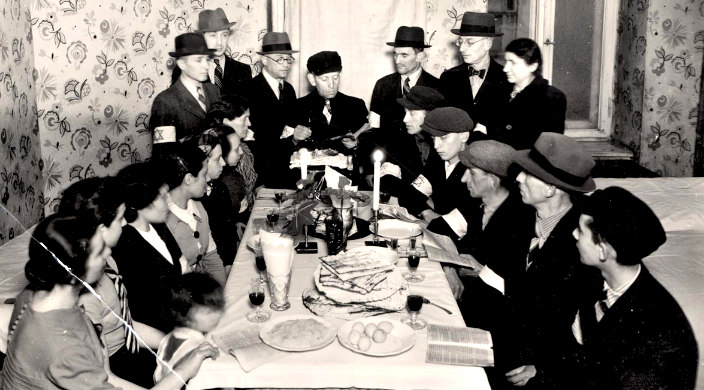 Black and white photo from Yad Vashem showing 1940s Jews observing a seder in the ghetto
