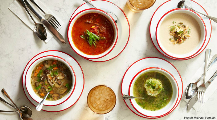 Overhead photo of four different soups in bowls with silverware, napkins, and drinks around the bowls