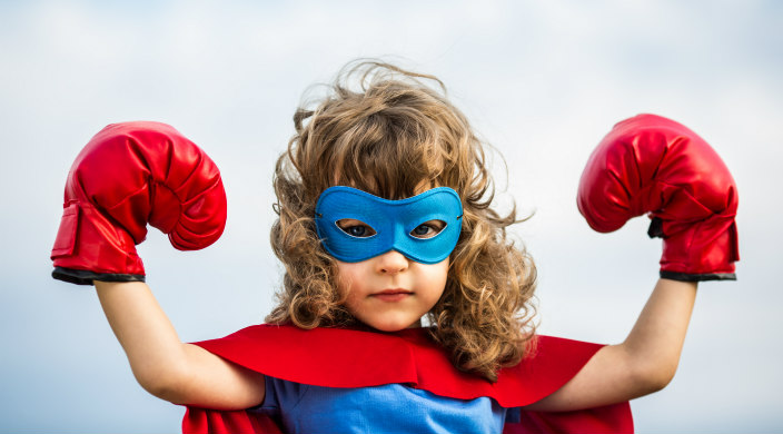 Young girl with blonde curls dressed in superhero costume with mask and boxing gloves