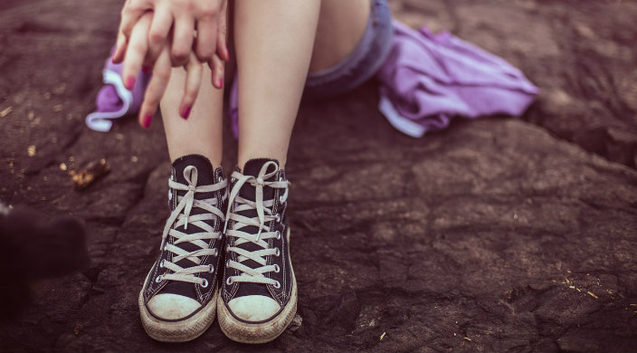 Closeup of the hands and Converse sneakers of a teenage girl sitting on asphalt