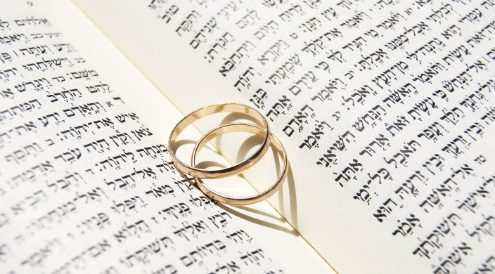 Two gold wedding band lying atop the spine of an open book with a heart shaped shadowed on the pages beneath them
