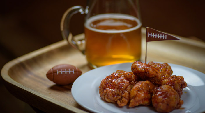 Plate of chicken wings next to a beer glass and a small plastic football