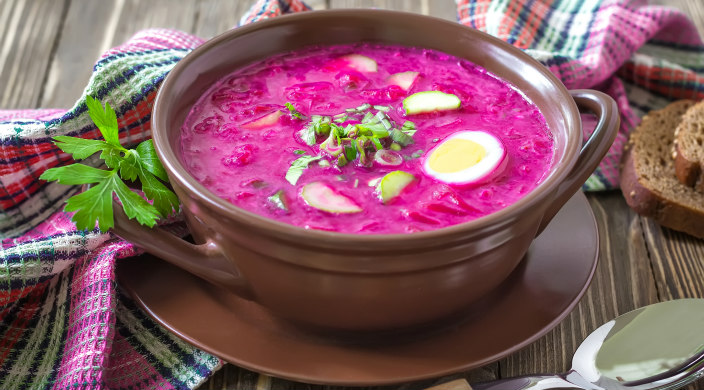 Bowl of bright pink borscht garnished with hard-boiled egg and greens