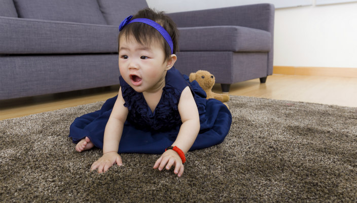 Chinese toddler on the floor in a living room