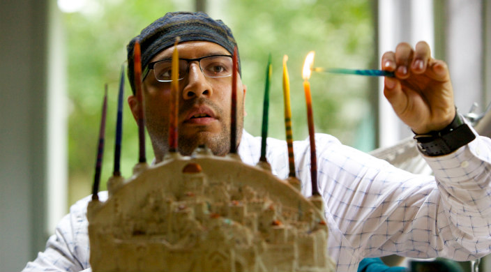 Young man kindling candles in a hanukkiyah