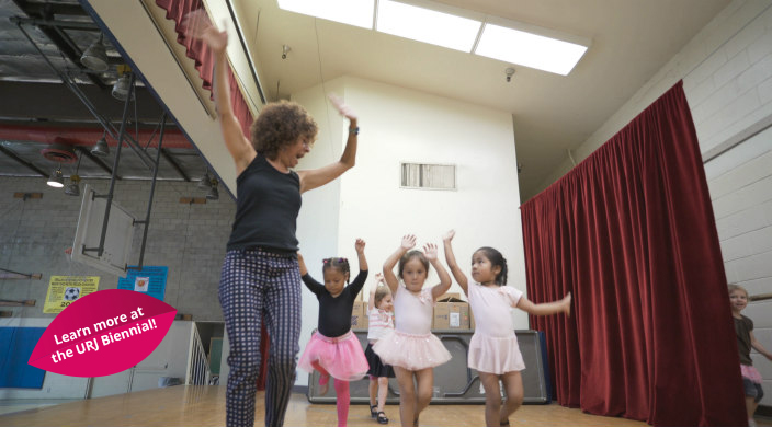 An older woman instructing preschool ballet students