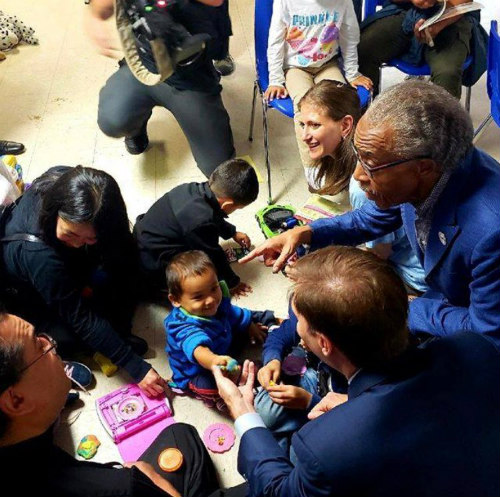 Faith leaders kneel on the floor as they play with immigrant children