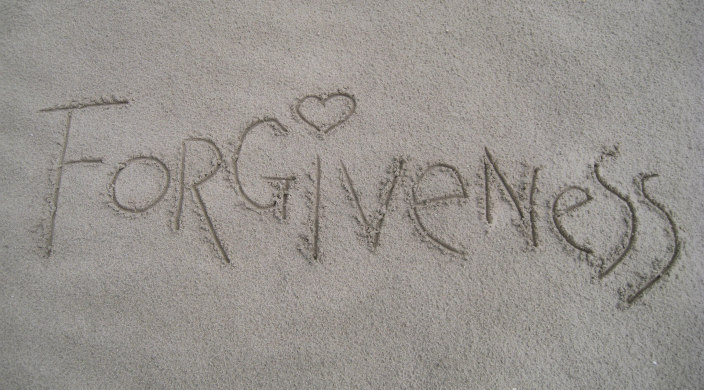 The word forgiveness written in the sand with a heart as the dot over the letter i