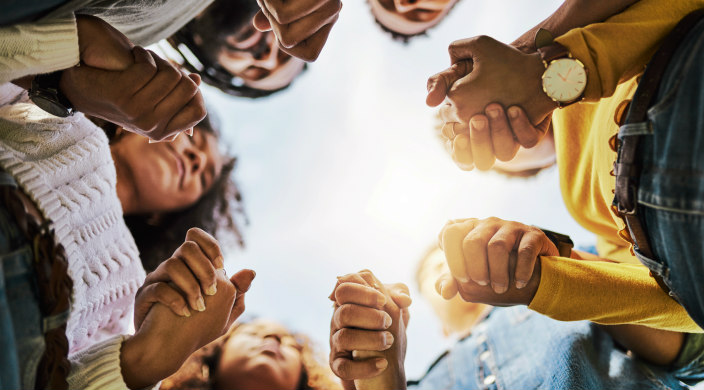 Shot from the ground up of a group of Black men and women holding hands as if in friendship or support