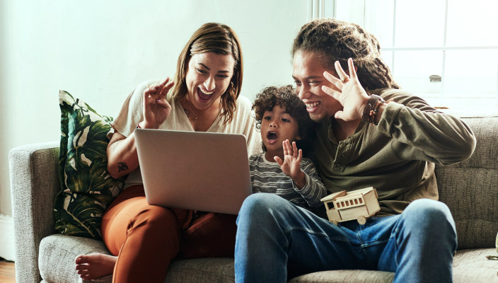 Multi-racial family gathered enthusiastically around a computer