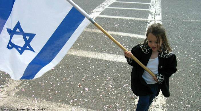 Young girl waving large Israeli flad on a pole