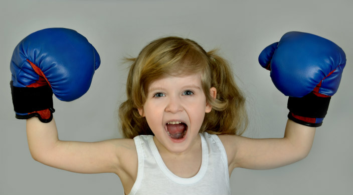 Elementary school-aged girl wearing blue boxing gloves with hands above her head
