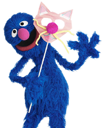 Grover, a character from Shalom Sesame, holding a mask for Purim, one kind of costume worn on the Jewish holiday