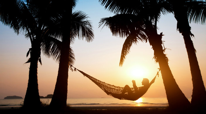 Silhouette of a person reading in a hammock strung between two palm trees on the beach at sunset