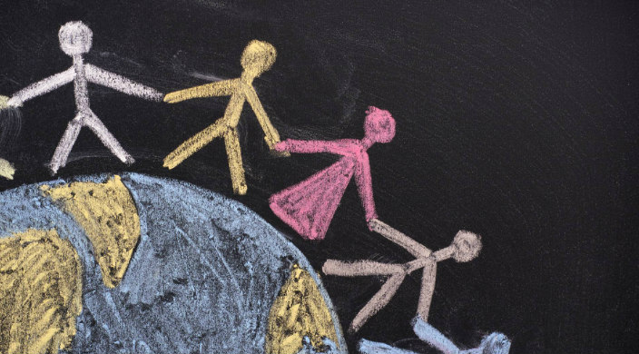 Chalk drawing of stick figures holding hands standing around the periphery of a map of the world