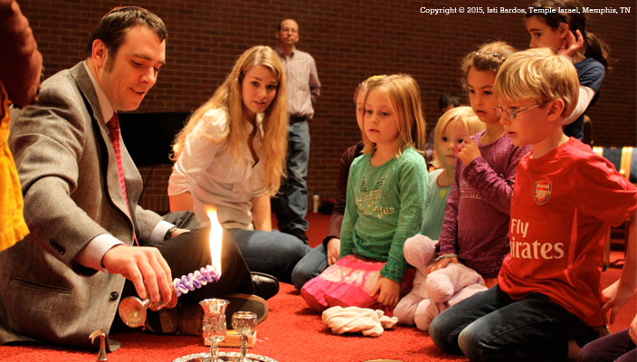 A rabbi with children dipping the Havdalah candle into a cup of wine