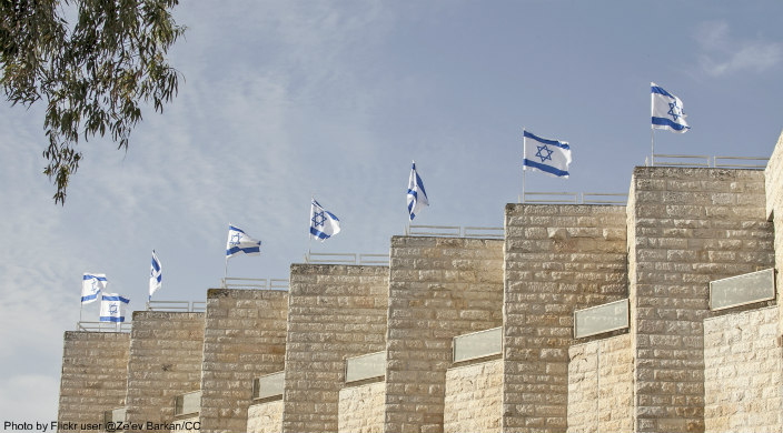 Jerusalem stone columns, each topped by a waving Israeli flag