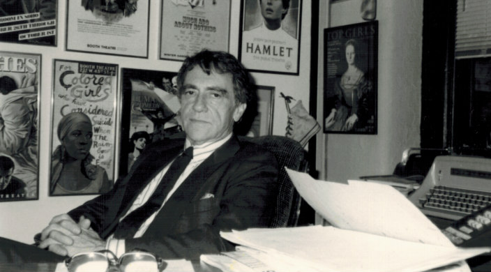 Black and white image of Joe Papp sitting behind a desk