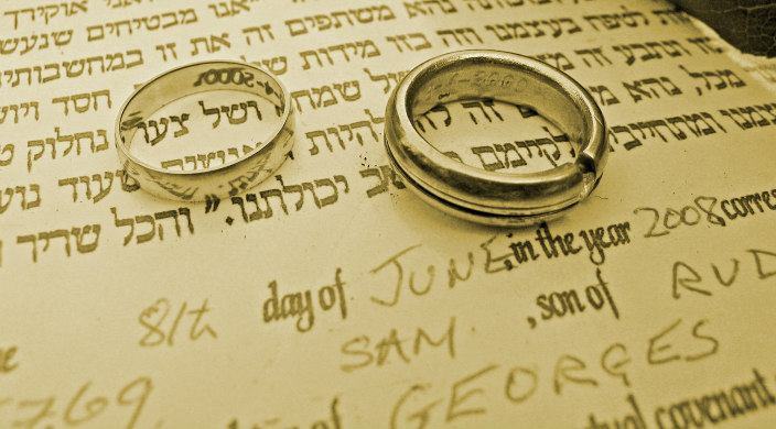 Ketubah (wedding contract) with two wedding rings on top of it