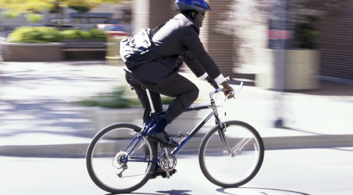 Man in business suit with messenger bag and helmet riding a bicycle