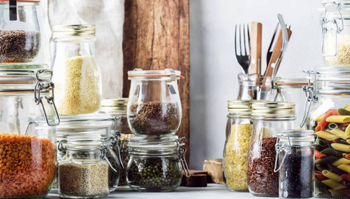 Image of rice pasta and other staples in containers in a kitchen pantry
