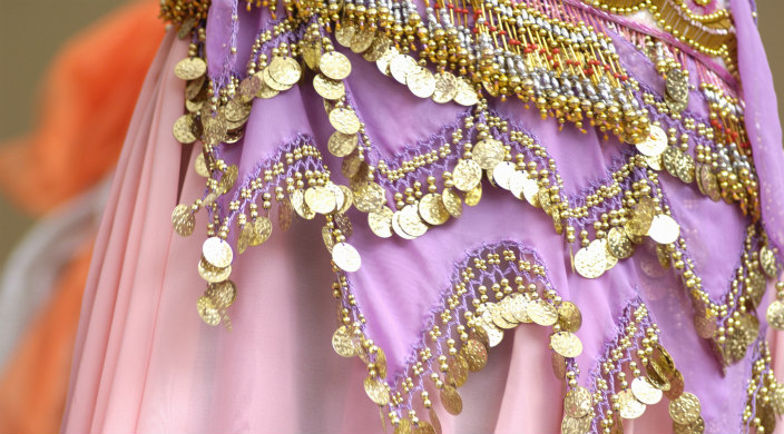 Partial view of woman's pink silky skirt with gold beading hanging from the tiers