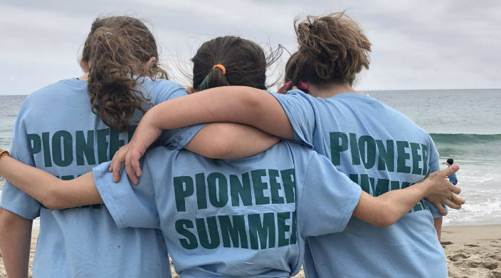 Three people facing a body of water with their arms around one another in shirts that say PIONEER SUMMER