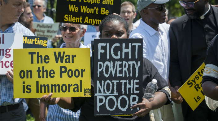 Protesters holding signs including one that says FIGHT POVERTY NOT THE POOR