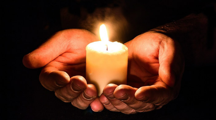 Upturned hands holding a lit candle in the darkness as in prayer or mourning