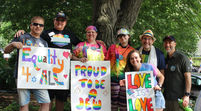 Individuals dressed in rainbow clothing and holding Jewish signs at a Pride rally