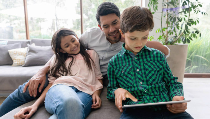 Dad and two smiling kids looking at an iPad together on the couch