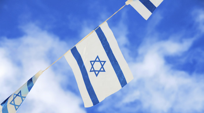 String of Israeli flags against a blue sky