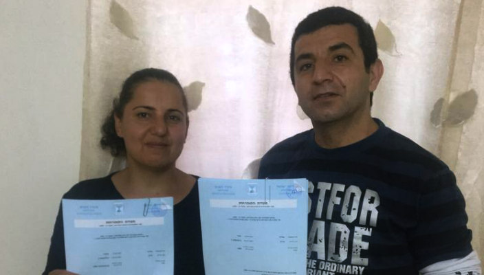 Sima and Oded hold the paperwork that made them Israeli citizens