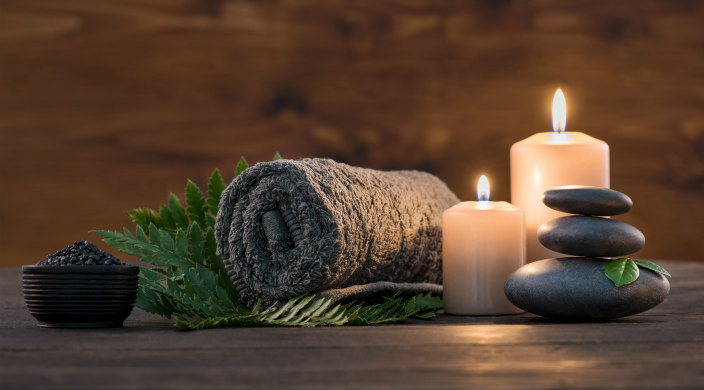 Spa towel, candles, rocks, and green leaves arrayed against a wood backdrop