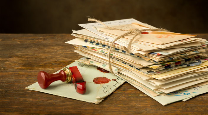 Stack of old letters tied with string; sealing wax and seal atop one loose letter