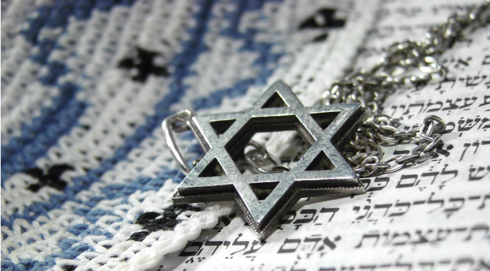 Star of David necklace lying on an open Torah and yarmulke