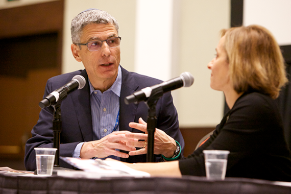 Rabbi Rick Jacobs talks to Rabbi Judy Schindler in front of microphones