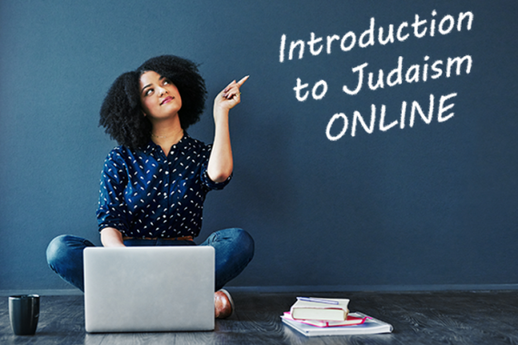 Woman sitting at laptop pointing to chalkboard that says Introduction to Judaism Online