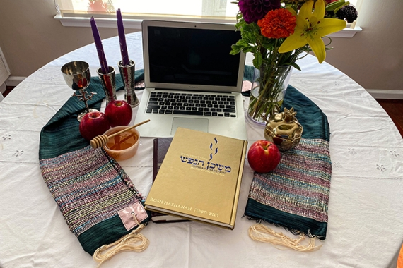 laptop computer, prayerbook, tallis, candles, and flowers on a table