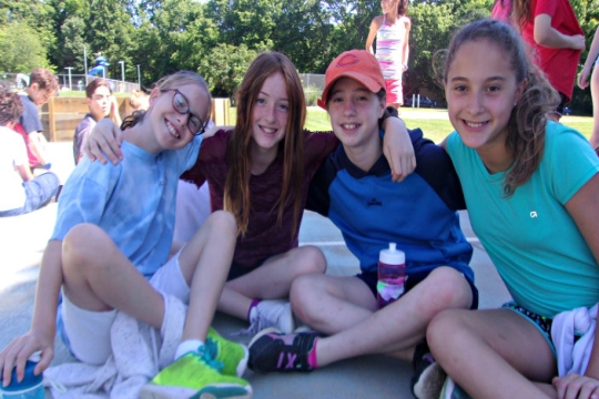 Four female campers of middle school age sitting on the sidewalk together with their arms around one another and smiling