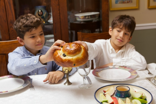 Two young boys holding a round challah with a platter of apples and honey in front of them
