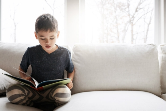 Child sitting cross legged on a white couch reading a picture book