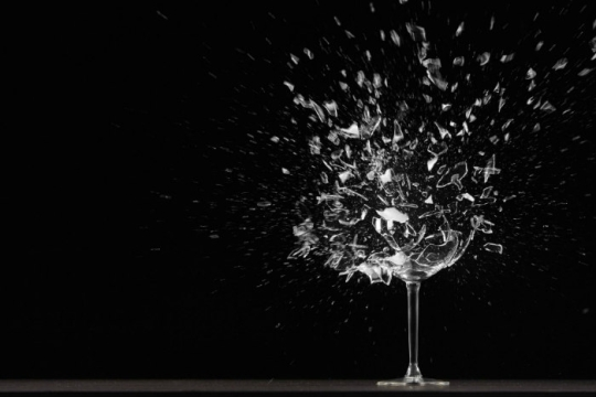 Wine glass exploding against a black background