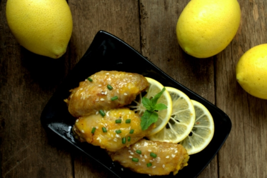 Chicken on a black plate with lemons