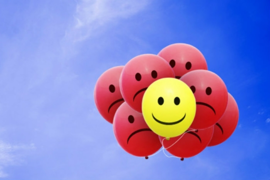 Cluster of balloons with frowning faces and one with a smiley face