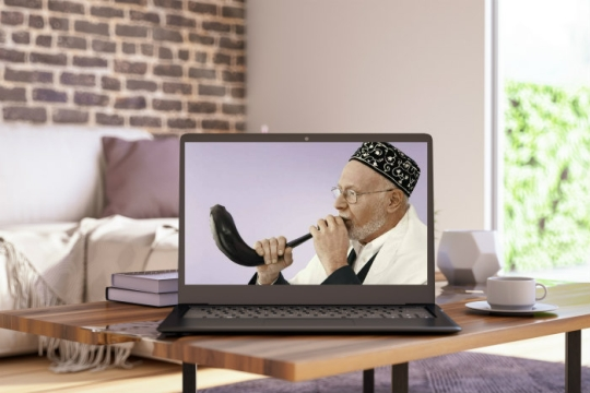 Laptop on a table in a living room displaying a man in a kippah blowing a shofar