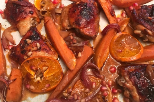 Orange pomegranate chicken lying on a sheet pan