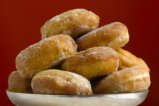 Pile of donuts on a silver platter against a red background