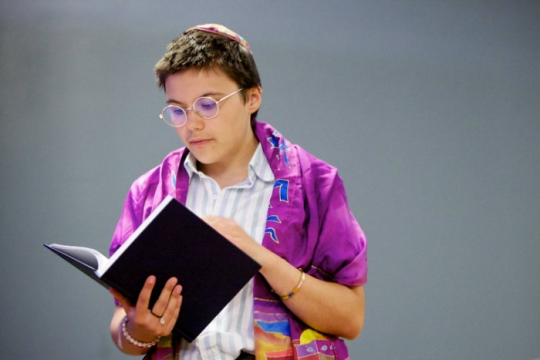 Person wearing a purple prayer shawl and holding a prayer book